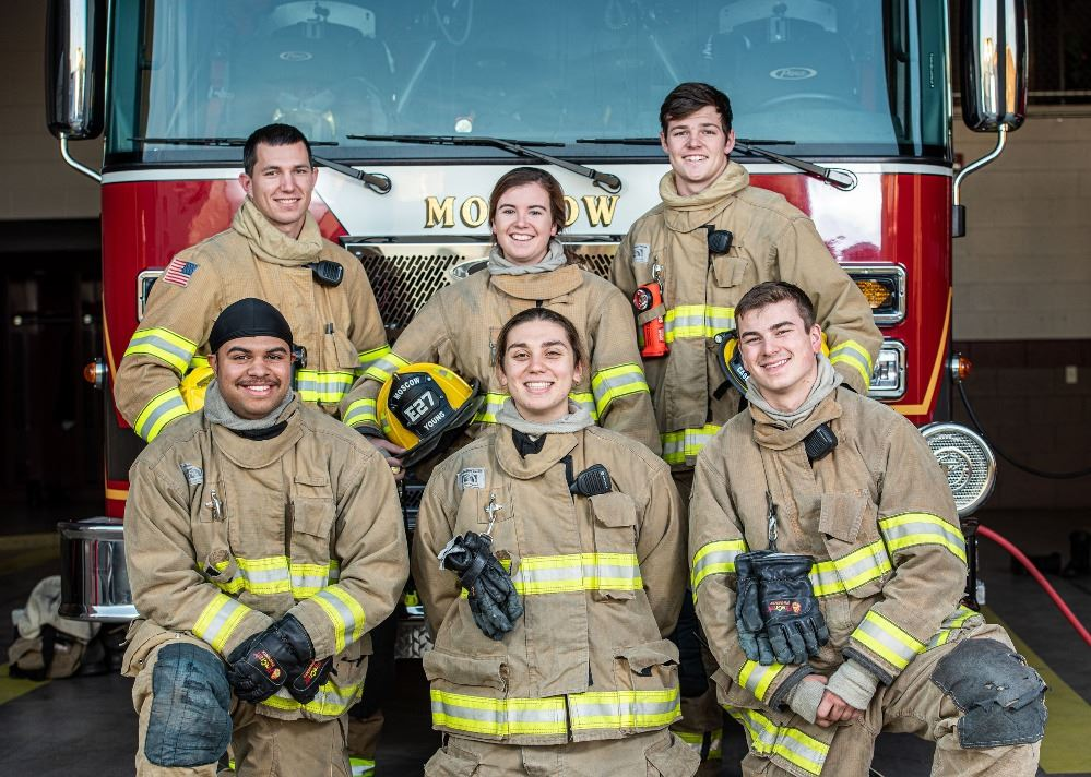 six student firefighters standing and kneeling in front of fire engine smiling