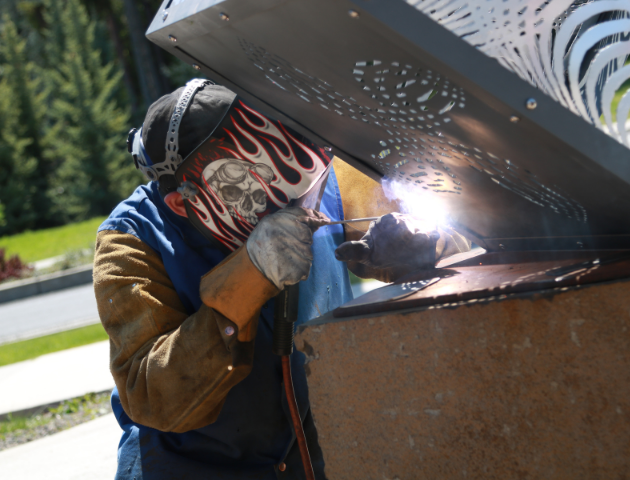 Man welding a sculpture to basalt pedestal